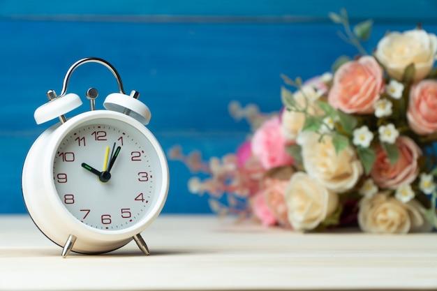 Sveglia e fiori bianchi rosa e rosa rossa sulla tavola di legno e sul fondo blu