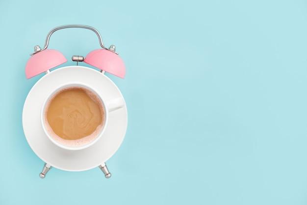 Sveglia e tazza di caffè rosa su copyspace blu. concetto di ora di colazione. stile minimal