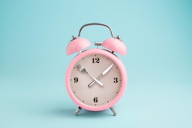 Sveglia. forchetta e coltello invece delle lancette dell'orologio. concetto di digiuno intermittente, ora di pranzo, dieta e perdita di peso