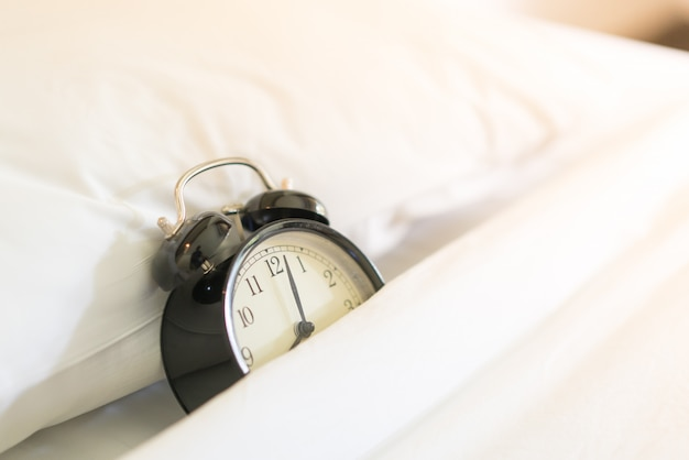 Sveglia in metallo su letto bianco 8:00.