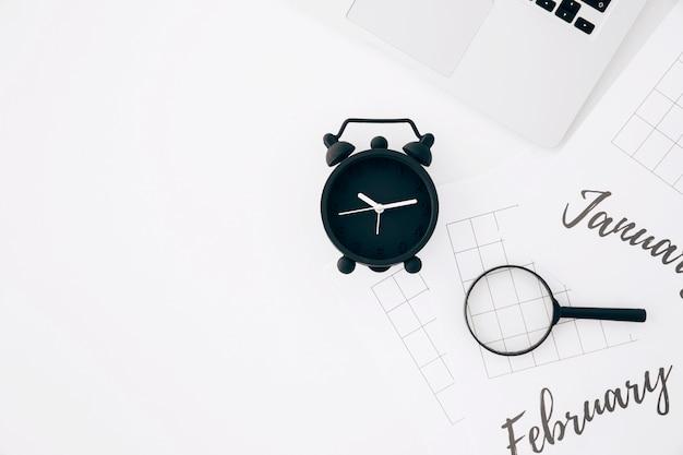 Sveglia nera; laptop e lenti di ingrandimento su carta contro sfondo bianco