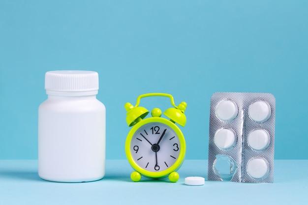 Sveglia, pillole, un barattolo di medicina su sfondo blu.