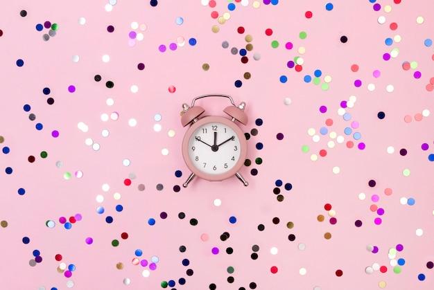 Sveglia rosa di disposizione piana di vista superiore di natale del nuovo anno con il fondo variopinto dello spazio della copia dei coriandoli