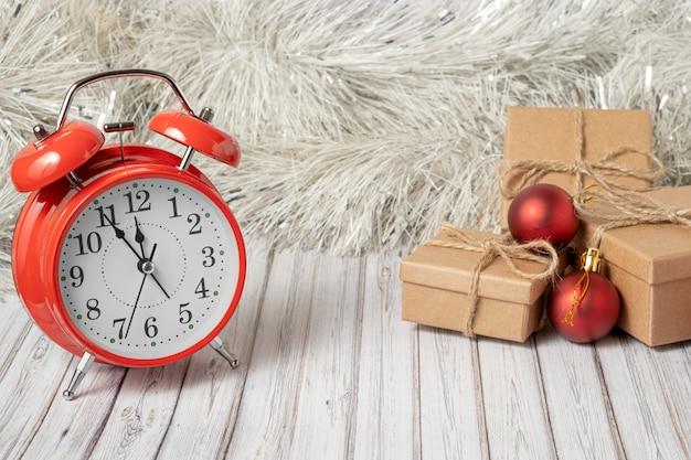Sveglia rossa d'annata e tre contenitori di regalo su una tavola di legno decorata con una ghirlanda e palle rosse di natale per il nuovo anno o natale. copia spazio