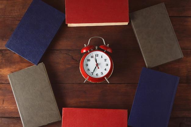 Sveglia rossa e libri distribuiti sulla superficie di legno scura. vista dall'alto