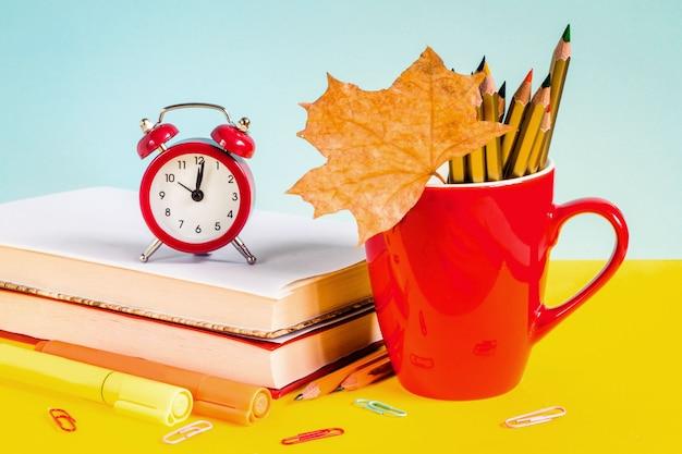 Sveglia rossa, matite colorate, libri e foglia d'acero su sfondo blu.