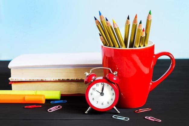 Sveglia rossa, matite colorate, libri e foglia d'acero su un fondo di legno nero.