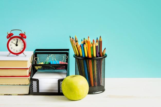 Sveglia rossa, mela, matite colorate, libri su sfondo blu
