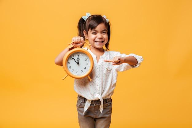 Sveglia sorridente dell'orologio della tenuta del bambino della bambina.