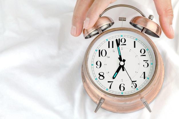 Sveglia su un letto con le mani di un uomo che tiene un orologio.