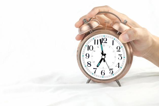 Sveglia su un letto con le mani di un uomo che tiene un orologio