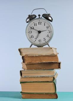 Sveglia sulla pila di vecchi libri sullo scaffale woden contro il muro bianco