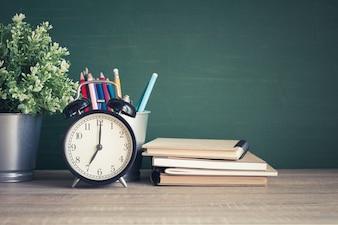 Sveglia sulla tavola di legno sul fondo della lavagna in aula