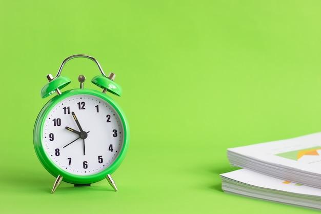 Sveglia verde con la pila di documenti finanziari su fondo verde