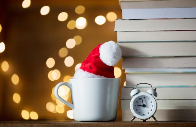 Sveglia vintage e pila di libri con tazza