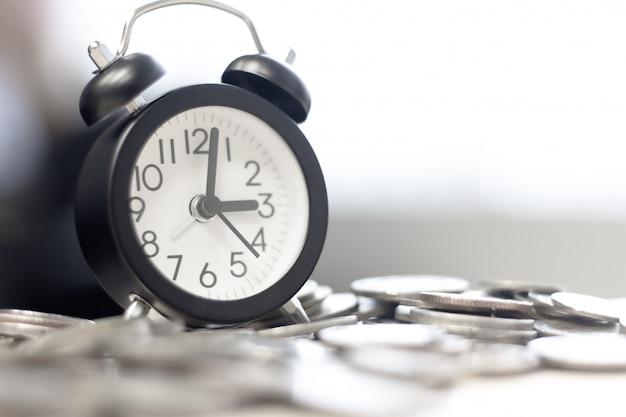 Sveglia vintage e pila di monete sul tavolo. investimento nel tempo e tempo trascorso.