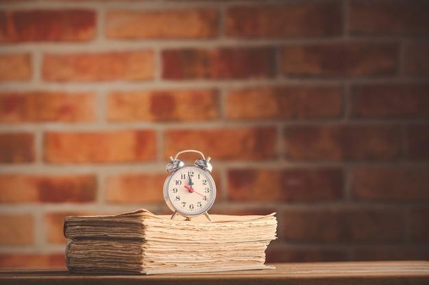 Sveglia vintage e vecchi libri sul tavolo di legno