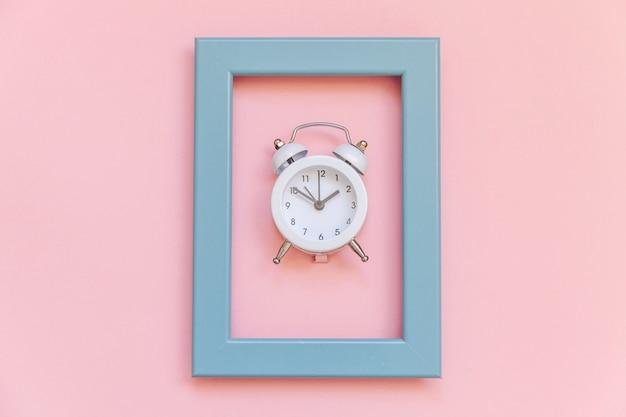 Sveglia vintage suoneria a campana gemella in cornice blu isolata su rosa pastello colorato alla moda