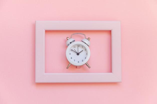 Sveglia vintage suoneria a campana gemella nel telaio rosa isolato su sfondo alla moda colorato pastello rosa