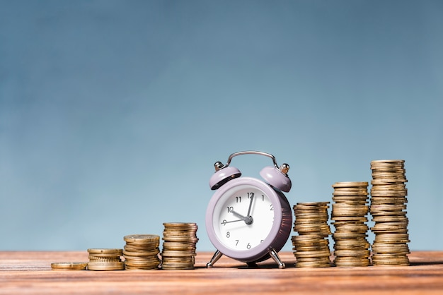 Sveglia viola fra la pila di monete in aumento sullo scrittorio di legno contro fondo blu
