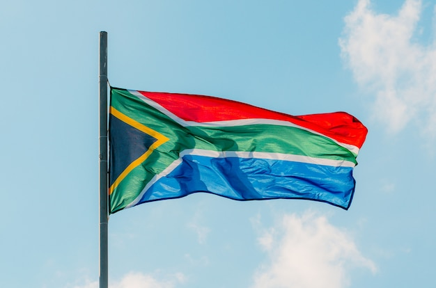 Sventolando la bandiera colorata del sud africa sul cielo blu.