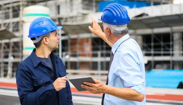 Sviluppatori di architetti che esaminano i piani di costruzione in cantiere usando un tablet