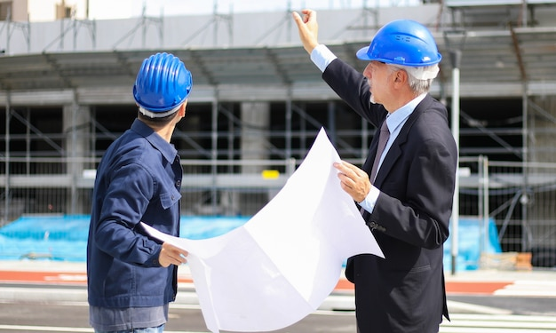 Sviluppatori di architetti che esaminano i piani di costruzione in cantiere