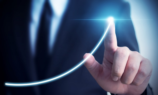 Sviluppo del business verso il successo e crescente concetto di crescita delle entrate annuali, uomo d'affari che indica il piano di crescita aziendale futuro grafico freccia