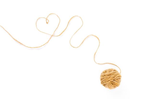 Svolgere la palla di filo, un filo forma un cuore su bianco