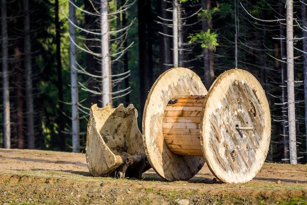 Svuotare il rotolo di legno utilizzato per i cavi elettrici e la pala dell'escavatore