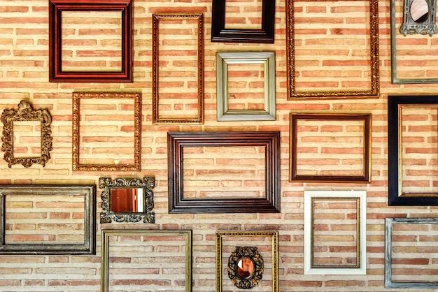 Svuotare vecchie cornici di legno per decorare originariamente un muro di mattoni interno.