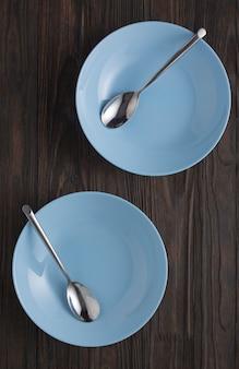 Svuoti i piatti blu con i cucchiai su una tavola di legno