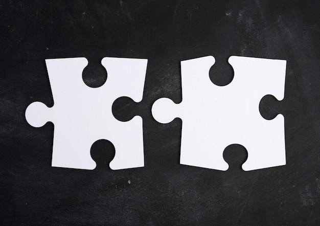 Svuoti i puzzle bianchi grandi della carta in bianco su un fondo nero