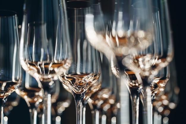 Svuoti i vetri puliti del champagne sul contatore nella barra.