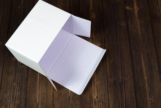 Svuoti il contenitore o il vassoio di regalo bianco per derisione sulla tavola di legno scura con lo spazio della copia.
