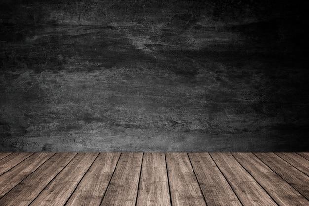 Svuoti il pavimento di legno con il fondo scuro del muro di cemento, per l'esposizione del prodotto.