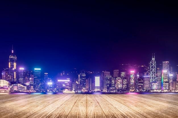 Svuoti il pavimento di legno della plancia con i fuochi d'artificio sopra paesaggio urbano al fondo di notte