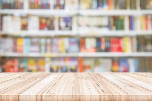 Svuoti il piano d'appoggio di legno con gli scaffali della sfuocatura nel fondo della libreria.