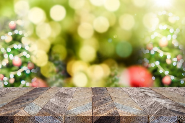 Svuoti il piano d'appoggio di legno di marrone scuro con la caduta rossa della palla e della neve della decorazione dell'albero di natale astratto della sfuocatura