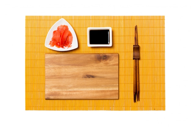Svuoti il piatto di legno marrone rettangolare con le bacchette per la salsa di sushi, dello zenzero e di soia sulla stuoia di bambù gialla. vista dall'alto con copyspace