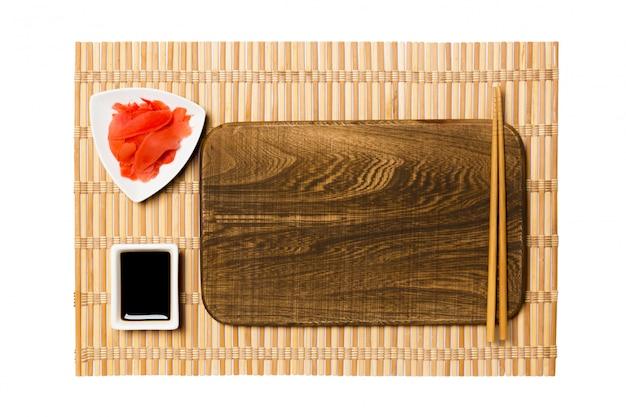 Svuoti il piatto di legno marrone rettangolare con le bacchette per la salsa di sushi, dello zenzero e di soia sulla stuoia di bambù gialla. vista dall'alto con spazio di copia per il tuo design