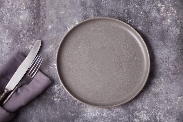 Svuoti il piatto e la coltelleria grigi sopra la tavola di cemento grigia