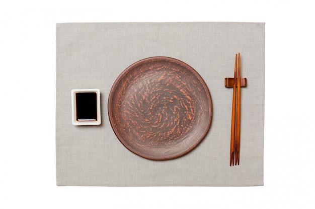 Svuoti il piatto marrone rotondo con le bacchette per i sushi e la salsa di soia sul fondo grigio del tovagliolo. vista dall'alto con copyspace