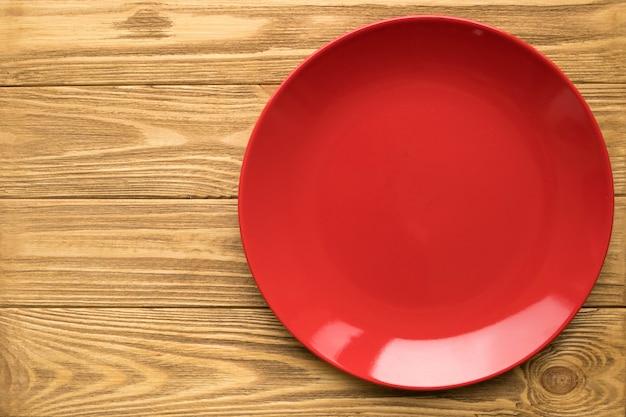 Svuoti il piatto rosso su una tavola di legno, vista superiore