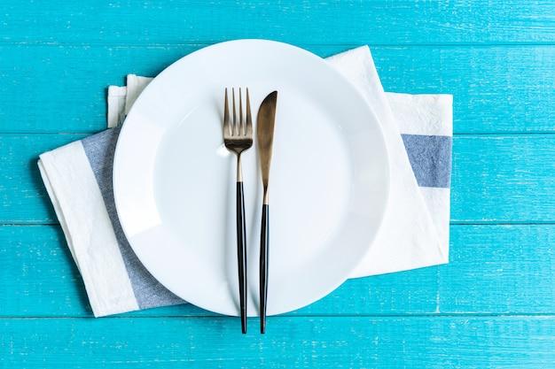 Svuoti il piatto rotondo ceramico bianco con la tovaglia, il coltello e la forcella sulla tavola di legno blu.