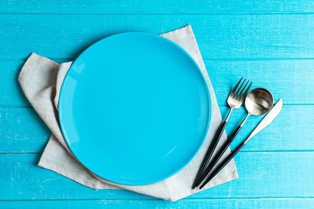 Svuoti il piatto rotondo ceramico blu con la tovaglia, il coltello, il cucchiaio e la forchetta sulla tavola di legno blu.