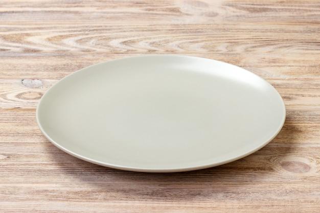 Svuoti il piatto rotondo per alimento su bachground di legno. vista in prospettiva
