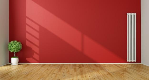 Svuoti il salone rosso con il radiatore sulla parete rossa