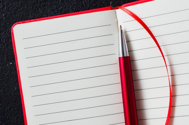 Svuoti il taccuino rosso aperto con la penna rossa su fondo scuro. carta bianca per il testo.