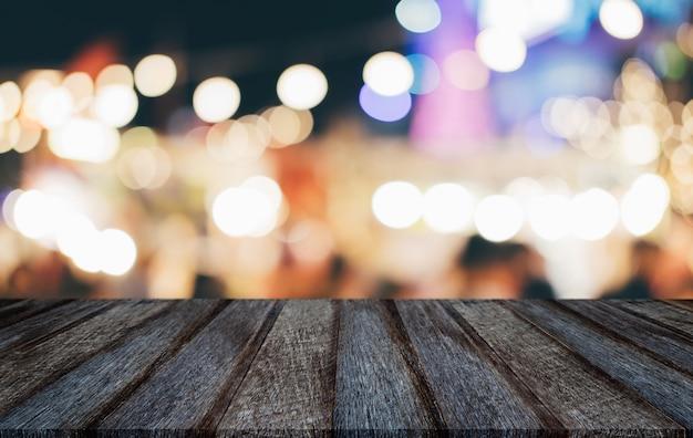 Svuoti il tavolo di legno davanti a fondo leggero festivo vago estratto con i punti luminosi e il bokeh